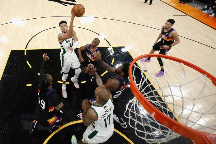 Giannis Antetokounmpo scoort over de Phoenix Suns' Chris Paul heen.