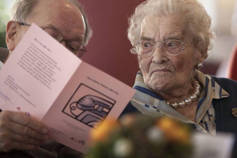 Bewoners bestuderen de folder van de Roze ouderentelefoon bij de High Tea. Beeld