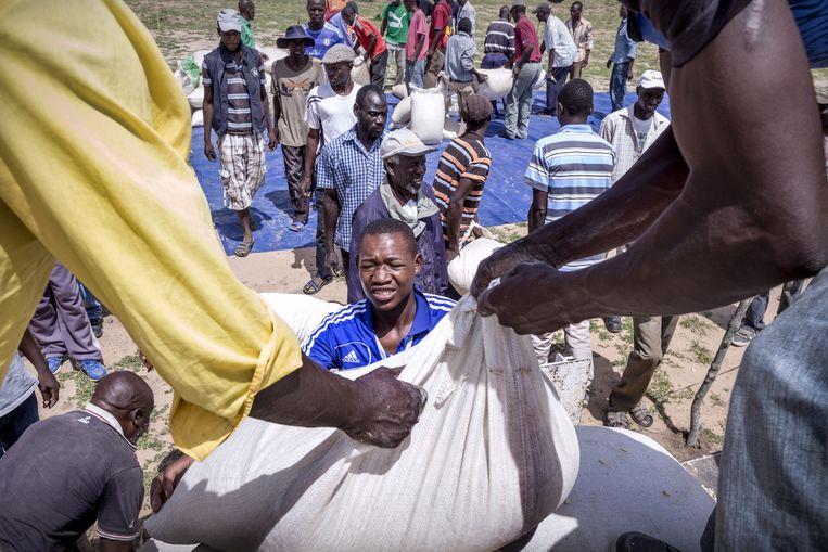 Mannen helpen bij het uitladen van een vrachtwagen met voedselhulp. Beeld Sven Torfinn