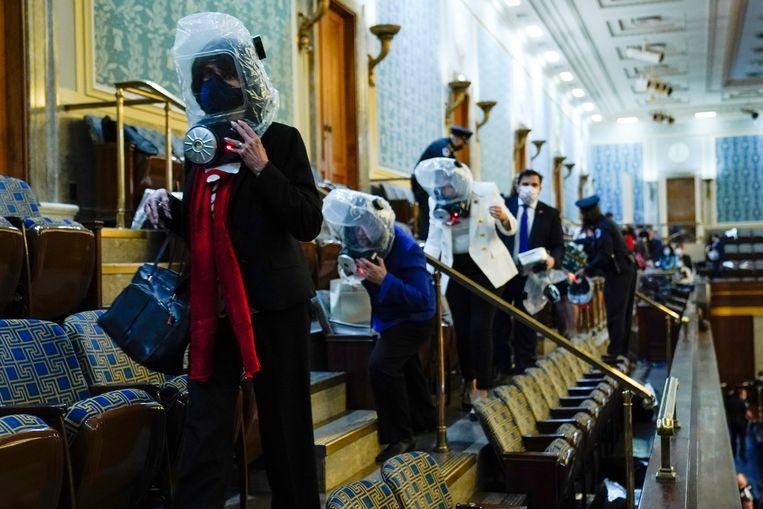 Aanwezigen met gasmasker worden geëvacueerd uit het Huis. Beeld AP