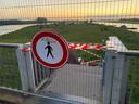 De ingang tot de landtong bij de IJssel vanaf de spoorbrug is na de overlast van vrijdagnacht afgesloten.