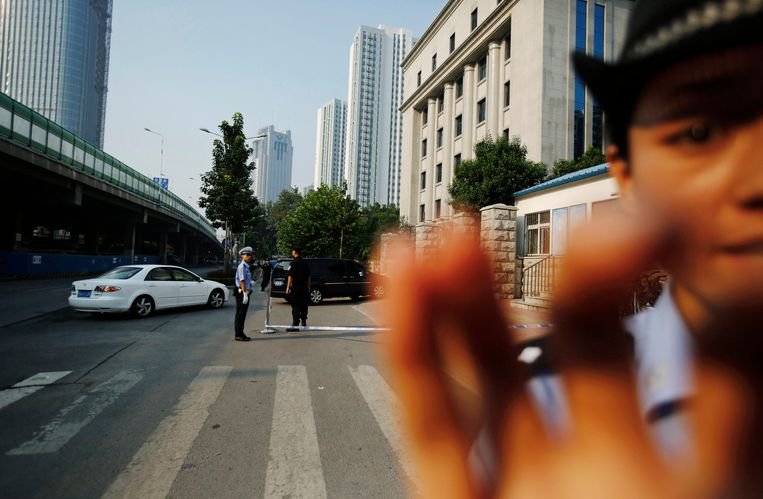 A policeman (R) tries to stop a journalist from photographing as vehicles enter a gate of the Jinan Intermediate People's Court, where the trial of disgraced Chinese politician Bo Xilai will be held in Jinan, Shandong province August 22, 2013. Police blocked entry to a courthouse in the eastern Chinese city of Jinan on Thursday where the trial of Bo is to open, the final, dramatic chapter of the country's most politically charged case in more than three decades. Bo, 64, is set to appear in public for the first time in 17 months in court, capping the country's biggest political scandal since the 1976 downfall of the Gang of Four at the end of the Cultural Revolution. REUTERS/Carlos Barria (CHINA - Tags: POLITICS CRIME LAW TPX IMAGES OF THE DAY) Beeld REUTERS