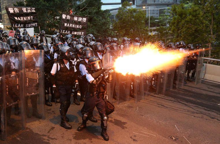 Politie vuurt traangas af richting betogers. Beeld REUTERS / Athit Perawongmetha