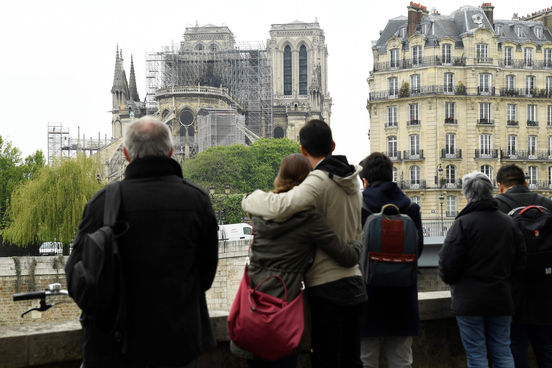 Passanten bekijken de Notre-Dame, waarvan het dak verwoest is in de brand. Beeld AFP