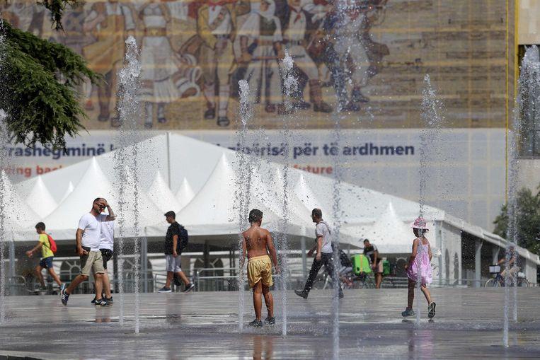 Kinderen zoeken afkoeling in Tirana, de hoofdstad van Albanië. De temperatuur steeg gisteren tot 39°C.  Beeld AFP