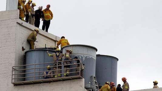 Brandweerlieden onderzoeken de watertanks op het dak van het Cecil Hotel in Los Angeles in februari vorig jaar.