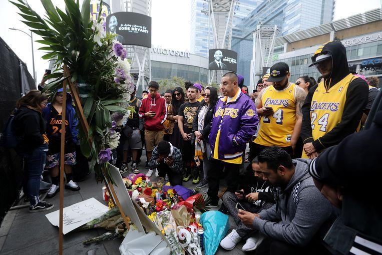 Fans van de LA Lakers leggen bloemen neer bij het Staples Center in Los Angeles. Beeld EPA