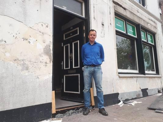 Paulus Hollander voor het op te knappen pand, waar de verf en het pleisterwerk van de wand zijn gevallen en de scheuren in de muren zitten.