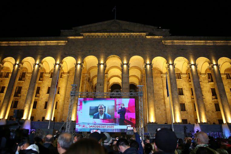 Voor het parlementsgebouw in Tbilisi kijken aanhangers van oppositiepartij Verenigde Nationale Beweging (UNM) na het sluiten van de stembussen naar een toespraak van partijleider en oud-president Michaïl Saakasjvili. Beeld AP