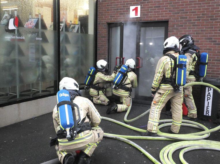 De brandweer gaat het schoolgebouw binnen.