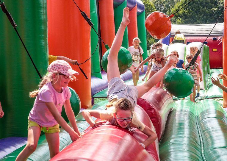 De kinderen gaan uit de bol op het reusachtige springkasteel.