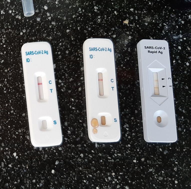 De Roche-test (rechts) en de FlowFlex-tests, op cola. Beeld