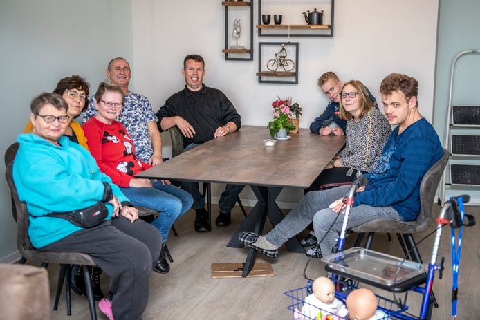 Kaoie-bewoners Jannie, Lida, Marco, Romy, Mathilde, en Daniel (vlnr) aan tafel in de huiskamer met begeleiders Anja (tweede van links) en Herman (vierde van links).