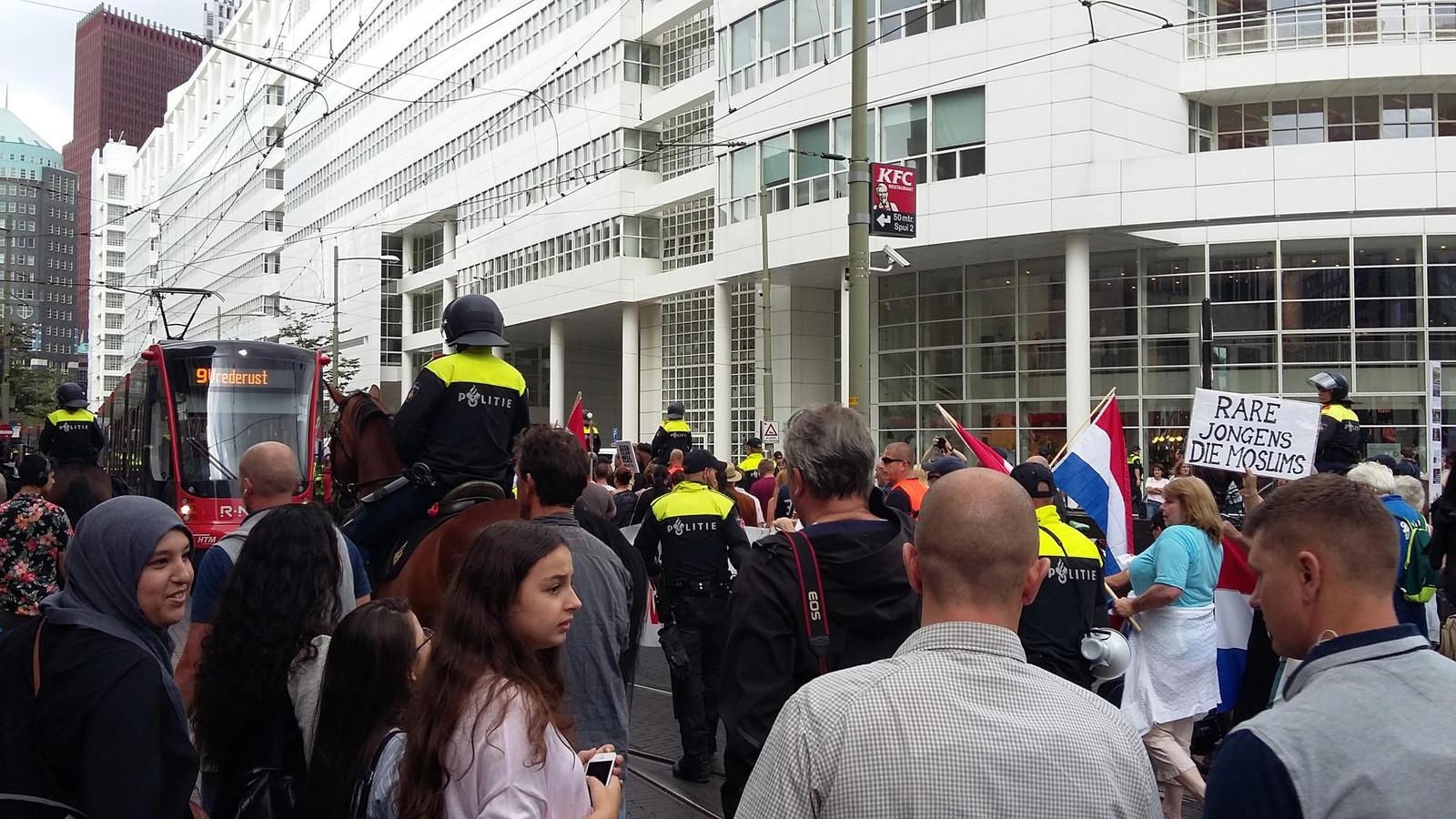 Het winkelend publiek kijkt de Pegida-betogers en hun omvangrijke politie-gevolg na in de Haagse binnenstad.