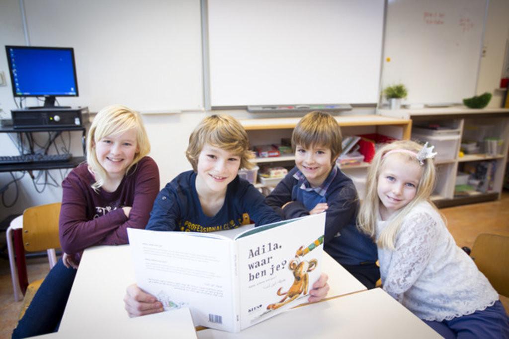 Tessa, Jesse, Nicolas en Nadine lezen het prentenboek gemaakt door asielkinderen