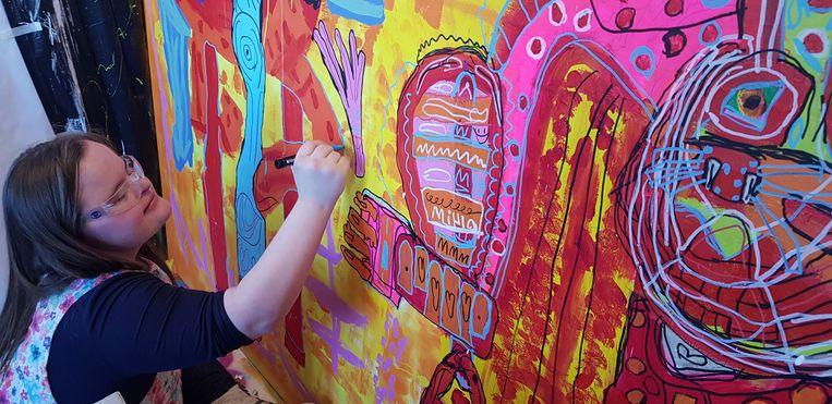 Mila Hartman met een van haar kleurrijke werken. Sue Smith: 'Qua achtergrond deed ze me denken aan Bruin Parry, een multitalent uit een creatief gezin.' Beeld -