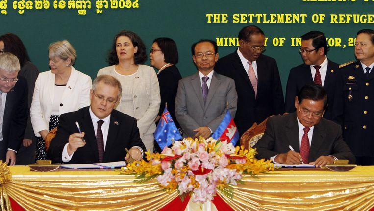 De Australische minister van Immigratie Scott Morrison (links) tekent in Cambodja een akkoord voor de opvang van immigranten. Beeld ap