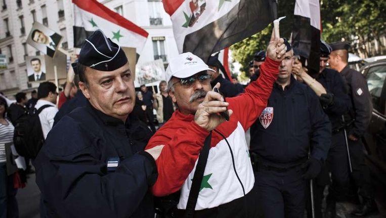 Bij een demonstratie in Parijs, gisteren, wordt een aanhanger van het Syrische bewind verplaatst door een Franse politieagent. Beeld afp