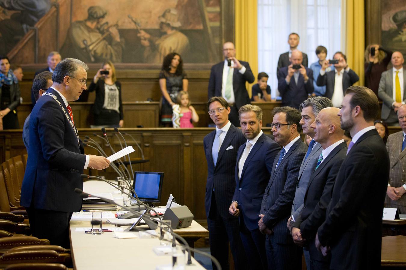 Burgemeester Ahmed Aboutaleb (links) spreekt de nieuwe Rotterdamse wethouders toe tijdens hun installatie.