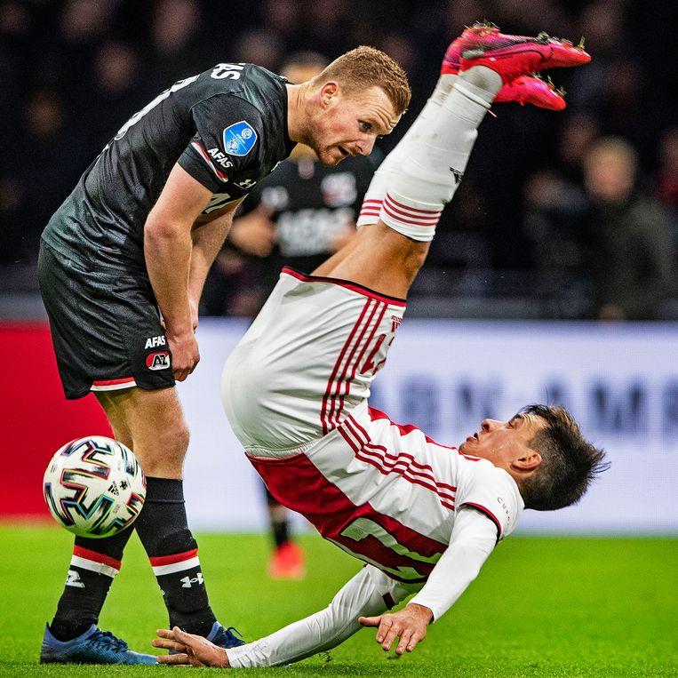 Lisandro Martinez (Ajax) maakt een smak. Dani de Wit (AZ) kijkt toe. Beeld Guus Dubbelman / de Volkskrant