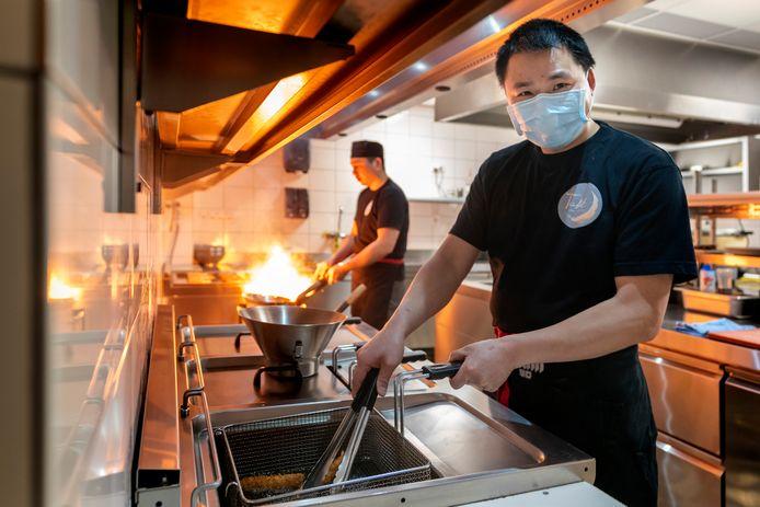 Eigenaar van Také Restaurant, Xinliang Liu, aan het werk in de keuken.