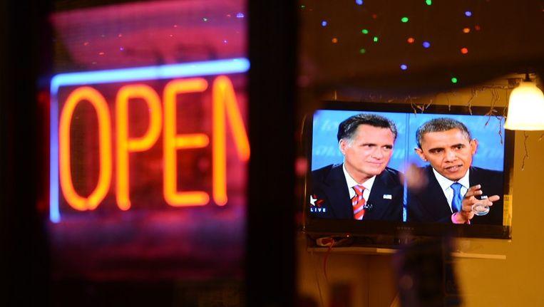 Een tv-scherm in een restaurant in Los Angeles toont het kandidatendebat. Beeld afp