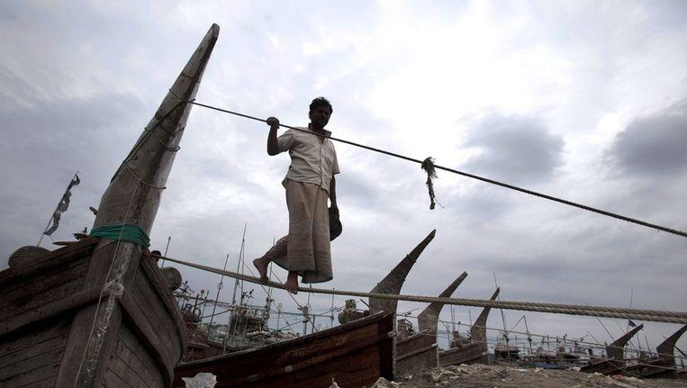 Een visser in Bangladesh maakt zijn vissersboot vast aan de oever van Kornofuli in Chittagong, Bangladesh Beeld AP