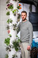 """David Van Steenkiste bij de plantentoren. """"Via een systeem kan je regelen dat elk plantje langs de binnenzijde van de buis water krijgt."""""""