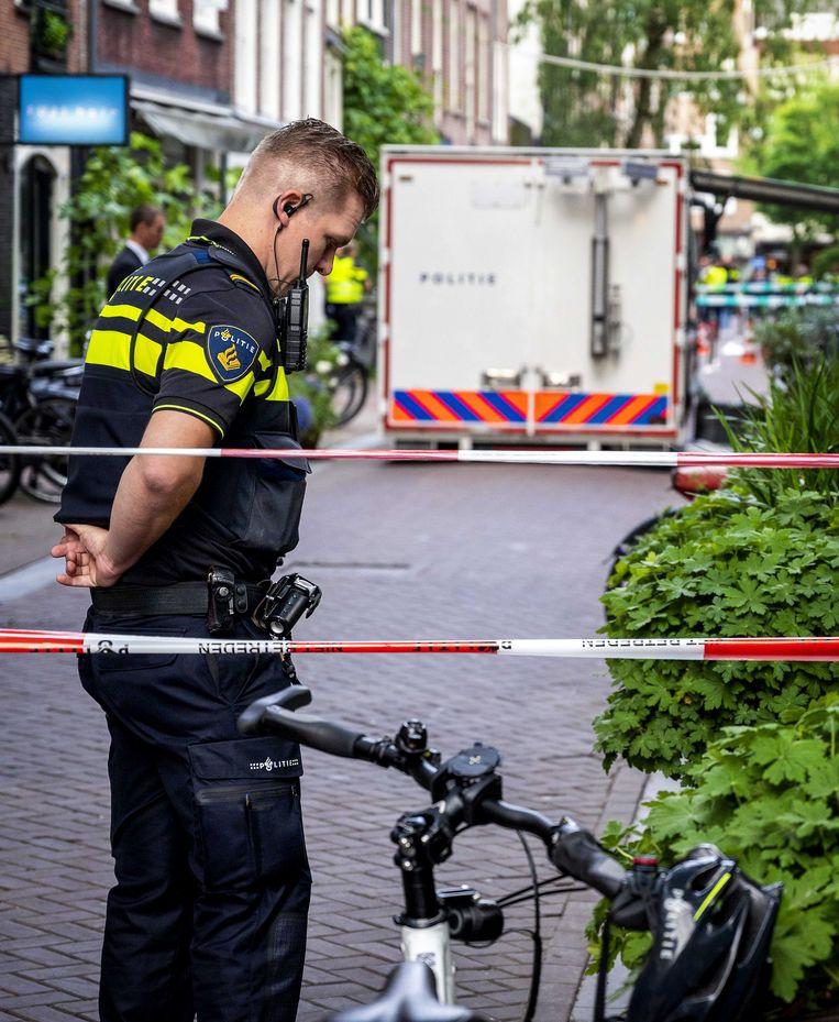 Politie bij de plaats waar Peter R. de Vries werd neergeschoten. De Volkskrant heeft de aanslag niet expliciet in beeld gebracht. Beeld ANP