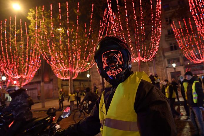 Een gemaskerde demonstrant bij de Arc de Triomphe zaterdag.