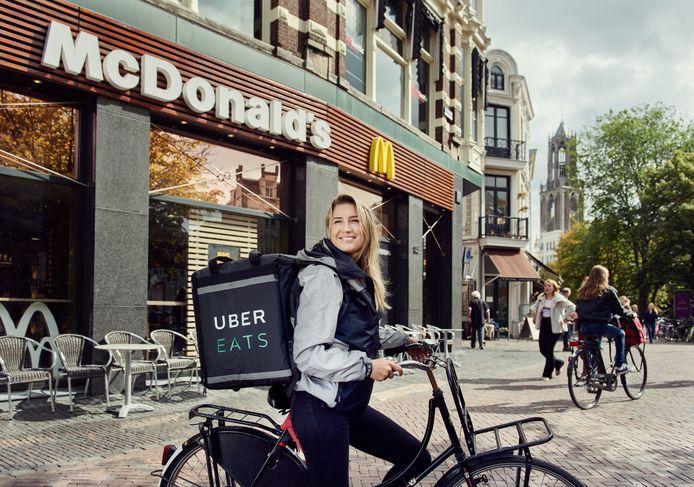 Een bezorger met op de achtergrond de Utrechtse Domtoren. McDonald's gaat nu ook bezorgen in Utrecht en Rotterdam. Den Haag en Eindhoven moeten snel volgen.