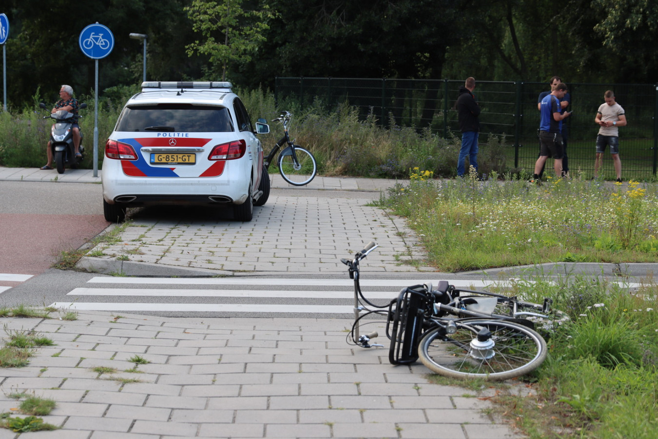 De fiets waarop moeder en twee kinderen zaten ligt op straat na de bijna-aanrijding in Ede.