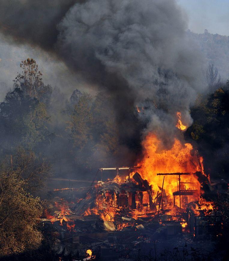 Een brandend gebouw langs de weg in Oakhurst. Beeld ap