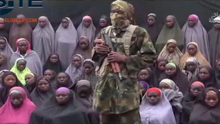 Een videobeeld uit 2016. Een Boko Haram strijder poseert gewapend voor een aantal Chibok meisjes die dan al twee jaar gevangen zitten.  Beeld AP
