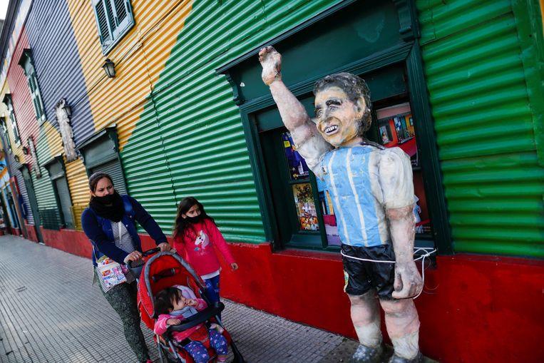 De Copa América zou oorspronkelijk in Colombia en Argentinië plaatsvinden. Een familie loopt hier langs een beeld van de overleden Argentijnse voetbalster Diego Maradona.  Beeld REUTERS