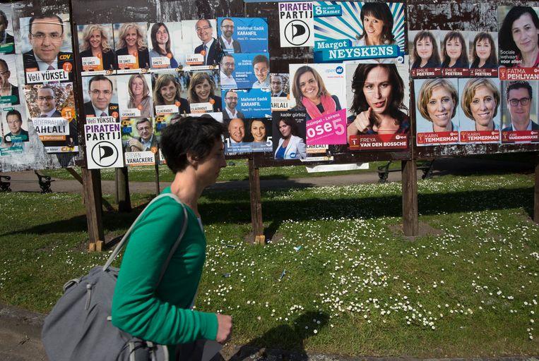 ► Een vrouw wandelt in Gent langs grote borden vol affiches voor de verkiezingen van 25 mei. Sommigen vinden ze interessant, anderen vinden ze niet meer van deze tijd. Beeld Photo News
