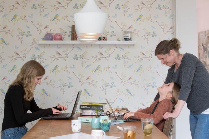 Thuisscholing bij de familie Stehmann door het Corona-virus. Zoë (links) en Lizzy doen hun werk nu aan de eettafel. Moeder Veronique mag tijdelijk voor juf spelen.