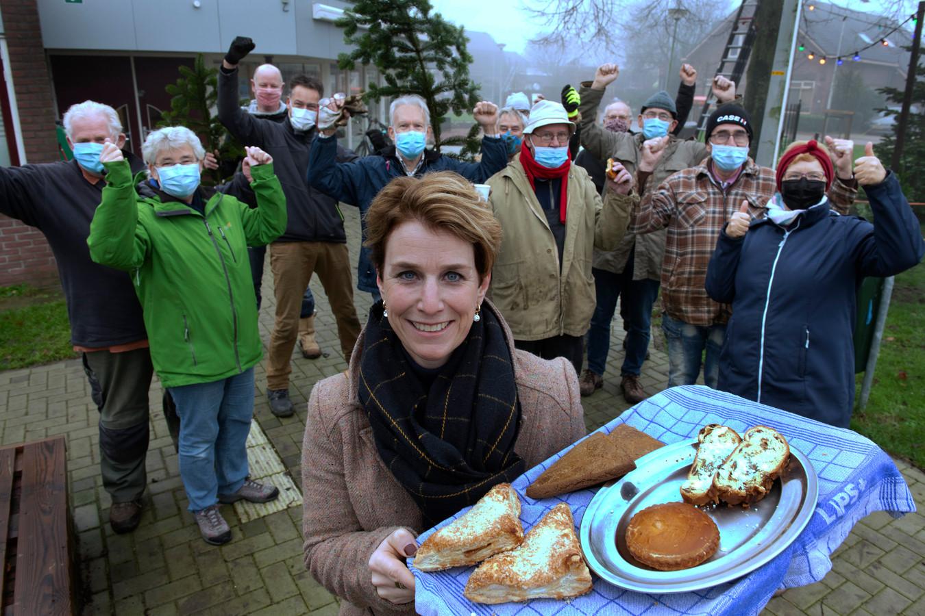 Vrijwilliger Haske van Dam bij het dorpshuis Tricht met vrijwilligers op de achtergrond tijdens de kerstboom opzetten.