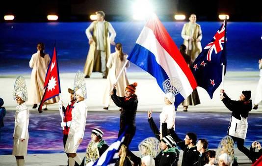 Schaatser Bob de Jong draagt de vlag bij de slotceremonie.