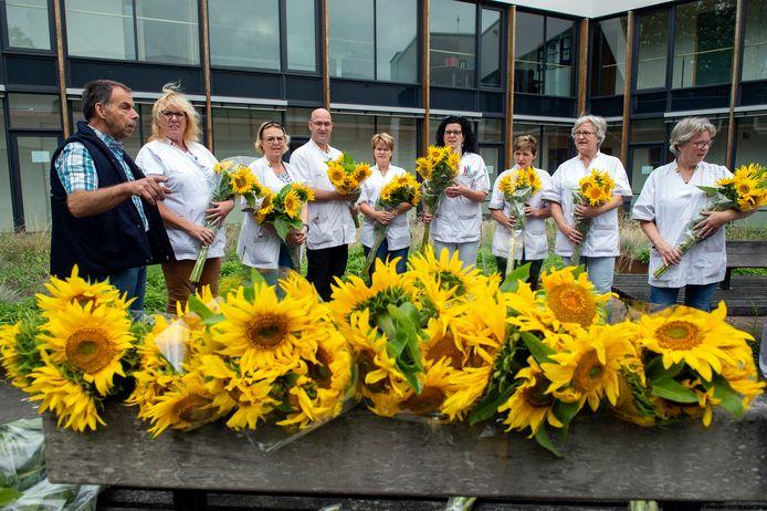 Boer Jack Verhulst (l) zet ongeveer 110 medewerkers van Thebe Thuiszorg in het zonnetje door ze een bos zelf geteelde zonnebloemen te geven.