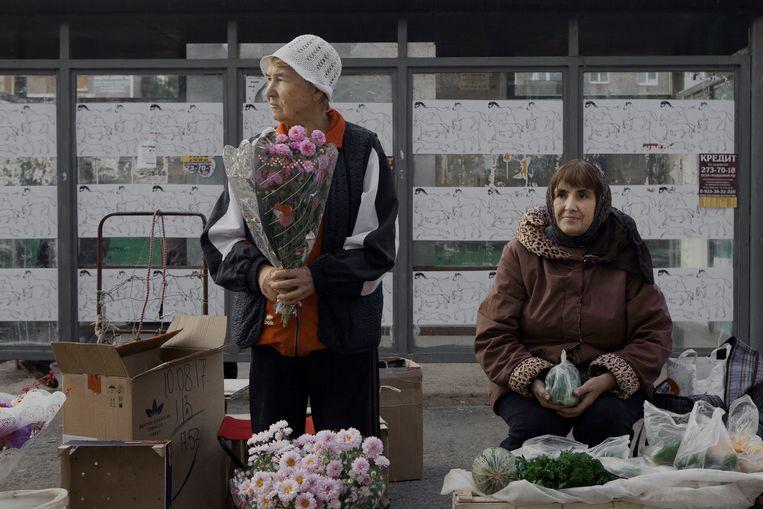 Oude dametjes verkopen bloemen, groenten en fruit op een geïmproviseerde markt in de Kosmonaut straat in Perm. Beeld Emile Ducke