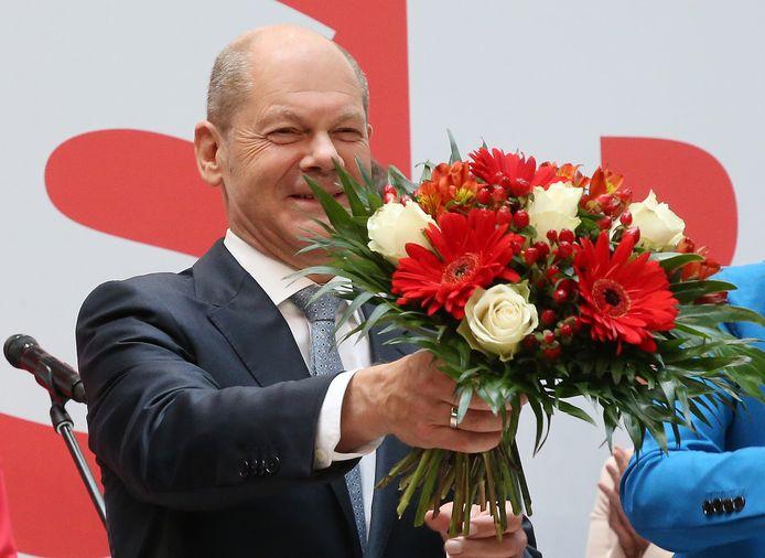 Sociaal-democraat Olaf Scholz wordt in de bloemen gezet als overwinnaar van de Duitse verkiezingen.