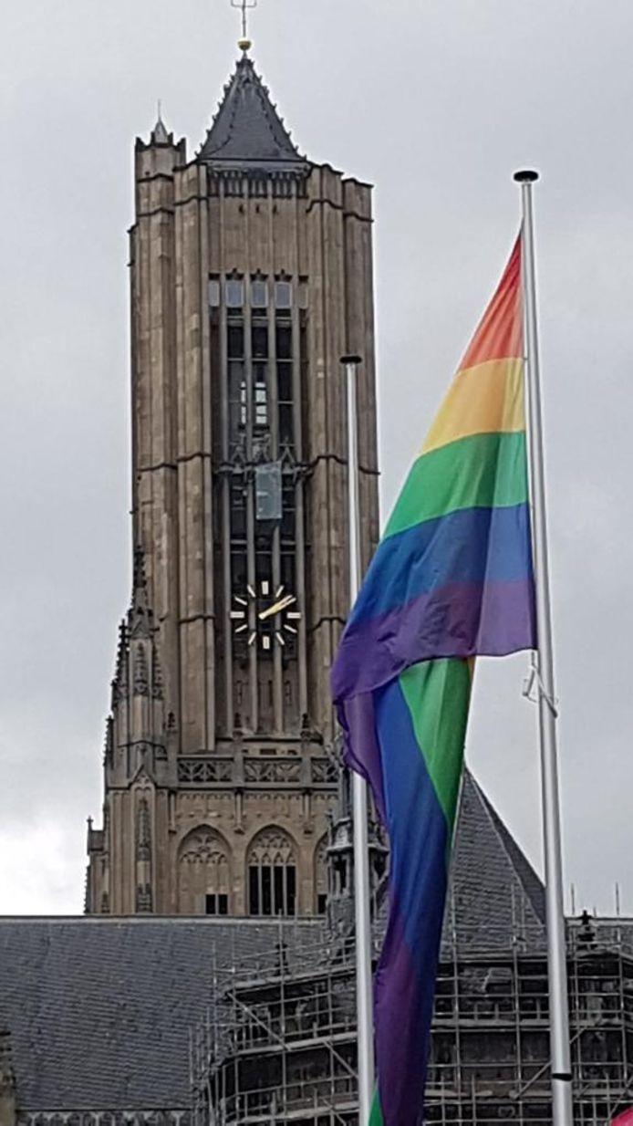 De regenboogvlag voor het Arnhemse stadhuis. Op de achtergrond de Eusebiuskerk