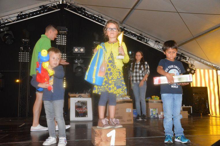 De winnaars van de driewielerkoers op het podium.
