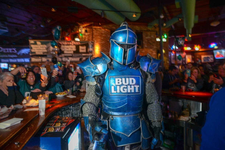Een man in harnas, bekend van Bud Light-reclames op de Amerikaanse televisie, deelt handtekeningen uit in een bar in Philadelphia. Beeld Getty Images