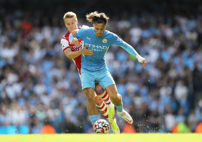Jack Grealish, de topaankoop van Manchester City, probeert te ontkomen aan Arsenal-speler Martin Odegaard.