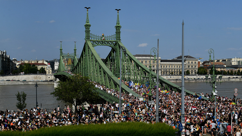 Een kleurrijke massa danst zaterdag over de Szabadsag ('Vrijheidsbrug') in Boedapest. Beeld AP