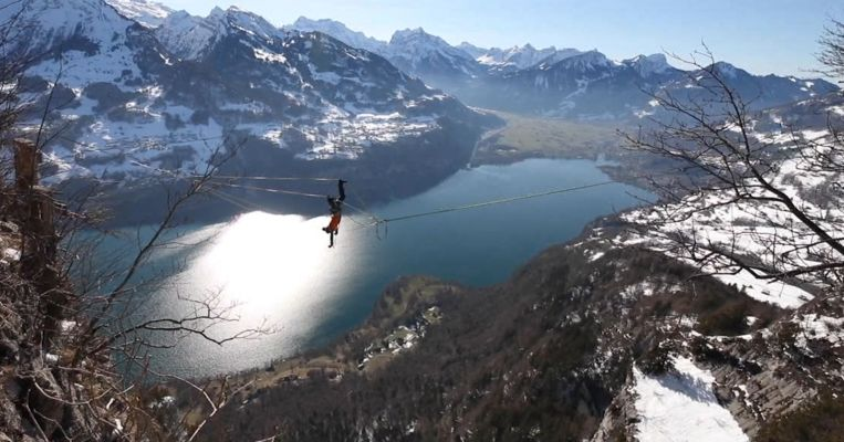 De man draait tientallen rondjes rond zichzelf en hangt daarbij met zijn armen en benen aan vier verschillende touwen.