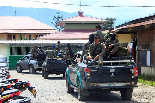 Bewapende agenten zoeken in Nduga naar de lichamen van de 31 afgeslachte bouwlieden.