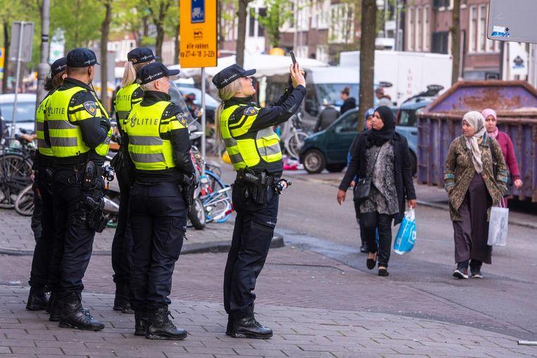 Een politieagent maakt tijdens Koningsdag een foto Beeld ANP